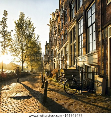 A stranger in the streets of the city Amsterdam, accompanied by long shadows, strolled between the canals and residential houses during this atmospheric sunset. - stock photo