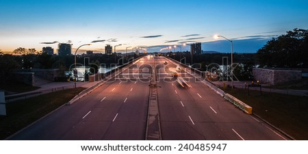 A stream of traffic as cars and trucks taverse the inter provincial bridge at dusk. - stock photo