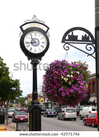 A street clock and an street sign with a big flowerpot hanging from it on a busy street in an small town. - stock photo