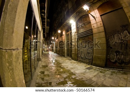"A street from the gothic quarter (""barri g?tic"") of Barcelona at night. The gothic cathedral of Barcelona is surrounded by old, narrow streets like these ones. This street is Carrer de la Freneria. - stock photo"