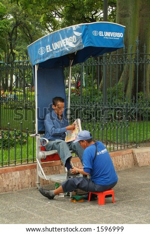 A street shoe-siner cleans a man's shoe while he reads a newspaper (Ecuador, South America) - stock photo
