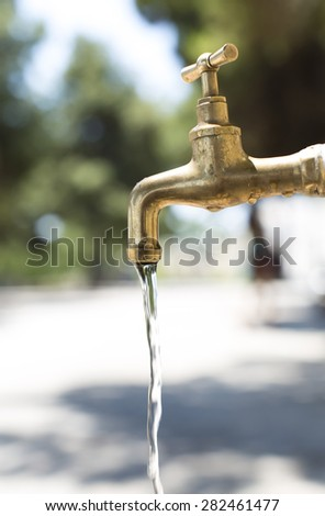 A street tap turned on and releasing water on a sunny day outdoors - stock photo