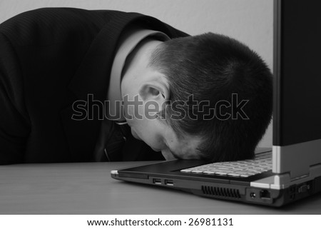 A stressed bald businessman with his forehead resting on the laptop computer keyboard - stock photo