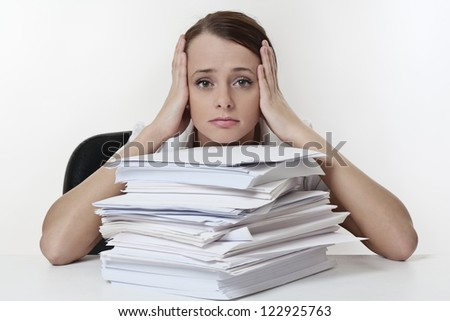 A stressed female with her head in her hands, sitting at her desk with a large  pile of paper work  stacked in front  of her. - stock photo