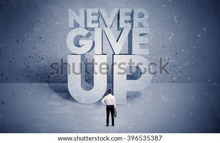 A stressed out business worker standing in front of huge block letters saying never give up in blue open environment concept - stock photo