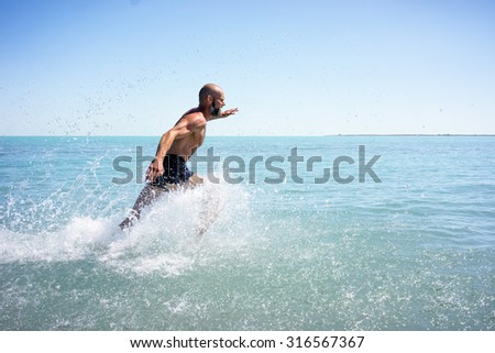 A strong man, athletic, makes a morning jog around the lake with a naked torso - stock photo