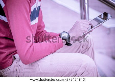 a student using a tablet on stairs - stock photo