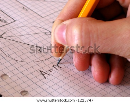 A student writing the formula for the area of a circle. - stock photo