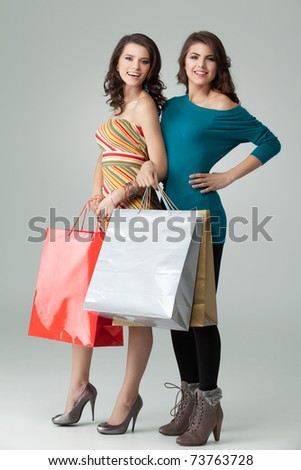 a studio image of two beautiful young women in high heels, holding a few shopping bags, smiling and looking happy. - stock photo