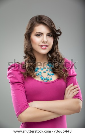 a studio portrait of a young, pretty woman, in colorful clothes and accessories, smiling, with her hands around her body - stock photo