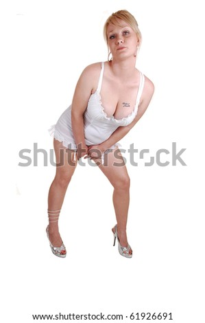 A studio shoot of a blond woman in white lingerie and an tattoo on her boobs, looking into the camera, on white background. - stock photo