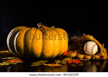 A studio shot of a pumpkin and a baseball glove and ball with fall leaves. - stock photo