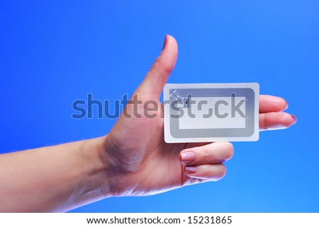 A studio shot of a woman holding in her hand Radio-frequency identification (RFID) tag card. Room for text, or your own message. - stock photo