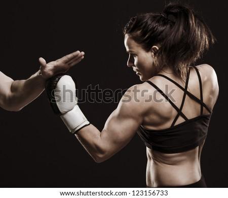 A studio shot of beautiful fitness woman training boxing. - stock photo
