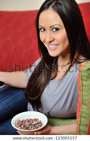 A stunning young biracial woman (Caucasian and Asian) smiles as she holds small bowl of salted almonds - stock photo