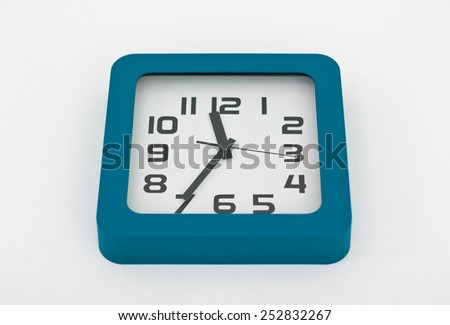 A stylish decorative wall clock hanging from a white wall. - stock photo