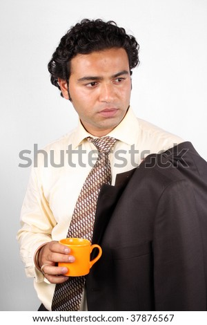 A stylish Indian businessman holding an orange coffee mug. - stock photo