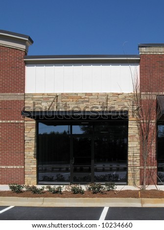A suburban shopping center made of textured brick, stone, and glass in the final stage of construction. - stock photo