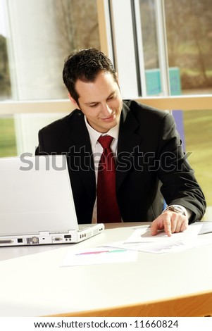 a successful business man is working on a table with a laptop - stock photo