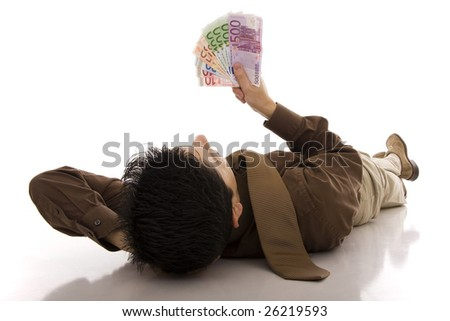 A successful business man lying on the floor looking to euros banknotes - stock photo