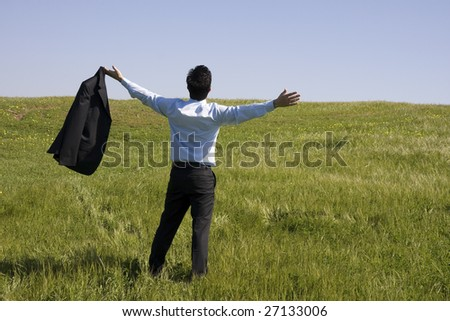 A successful business man with his arm outstretched on a green field - stock photo