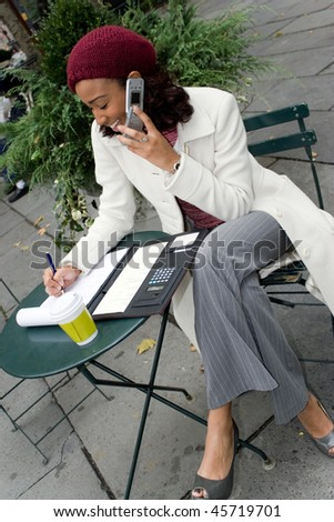 A successful career woman conducting business outdoors at a table with her cell phone and coffee. - stock photo