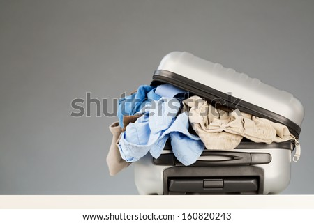A suitcase over-packed with various casual clothes lying on a white surface with a gray background. - stock photo