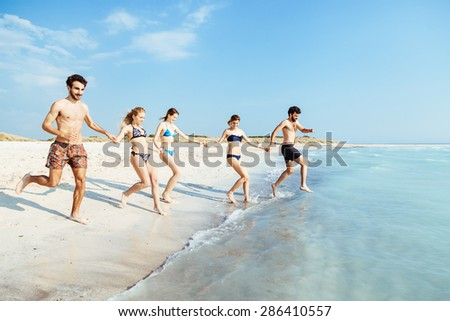 A summer day on a sandy beach, a group of five young people run towards the sea to swim. People are in swimwear on the beach and there are no other people - stock photo