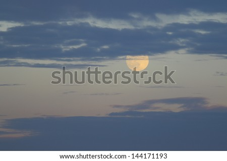 A summer perigee moon as seen in the night sky through the cloud filled sky over the Chesapeake Bay from Gloucester Virginia - stock photo