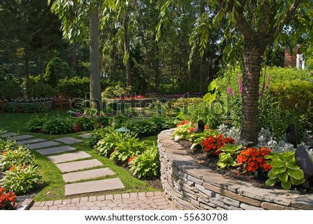 A Summer view of an ornamental garden with a slate pathway and garden wall made out of stone. - stock photo