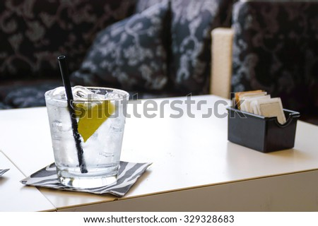 a sun lit ice cold glass of water or cocktail with ice and lemon on a table in a dark room, with copy space for text. Artistic dark contrast mood. - stock photo