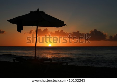 a sunset in Barbados with the silhouette of a parasol and two sunbeds focused on the parasol with the sun and clouds de-focused - stock photo