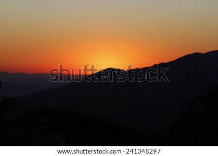 A sunset in mountains - stock photo