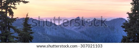 A sunset panorama looking North From Hurricane Ridge over Unicorn Peak toward the foggy Strait of Juan de Fuca and Vancouver Island in Olympic National Park, WA - stock photo