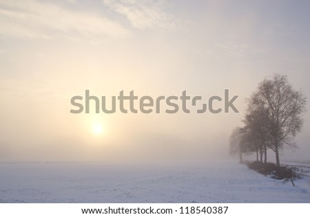 A sunset through the fog after a foggy and cold winter day - stock photo