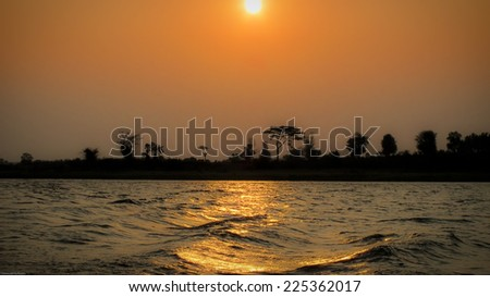 A sunset with trees silhouetted against the sky and water in the foreground. - stock photo