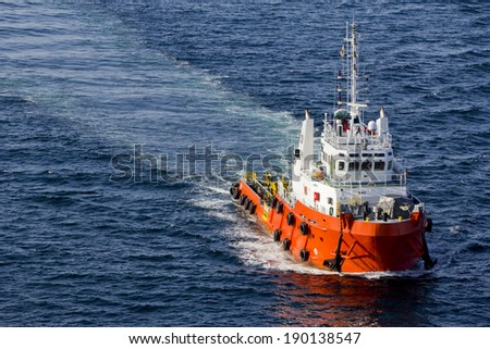 A supply boat in the midst of an open sea - stock photo