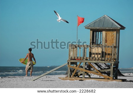 A surfer, a seagull, and a watch tower on the beach - stock photo
