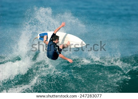 A surfer boosts a radical aerial move. motion blur - stock photo