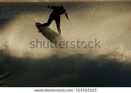A surfer flies above a wave at sunrise. - stock photo