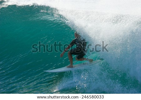 A surfer guides himself and his surfboard through a beautiful blue tube on an ocean wave. - stock photo