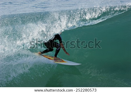 A surfer in a wetsuit rides a tube on a beautiful ocean wave. - stock photo
