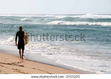 A surfer on the beach checking out the waves - stock photo