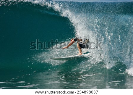 A surfer rides a tube on a beautiful, blue wave in the ocean. - stock photo