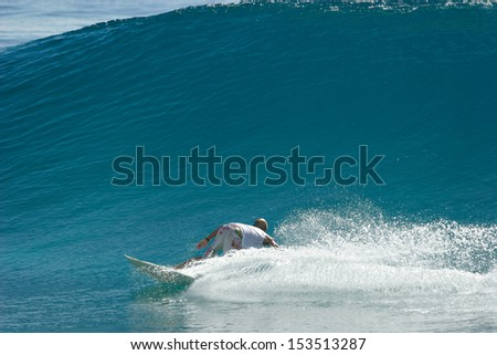 A surfer rides a wave. - stock photo