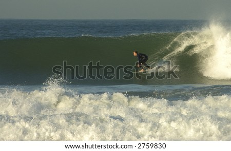 a surfer riding a big wave - stock photo