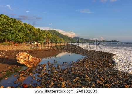 A surfer's destination, Playa Dominical in Costa Rica is a rocky beach settled mostly by foreign surfers. - stock photo