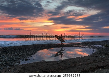 A surfer's destination, Playa Dominical in Costa Rica is a rocky beach settled mostly by foreign surfers. Sunset scene with surfers, waves and the setting sun reflecting in a tide pool. - stock photo