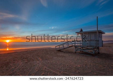 A surfer sits on a Manhattan Beach, California lifeguard tower at sunset with Malibu in the background. - stock photo