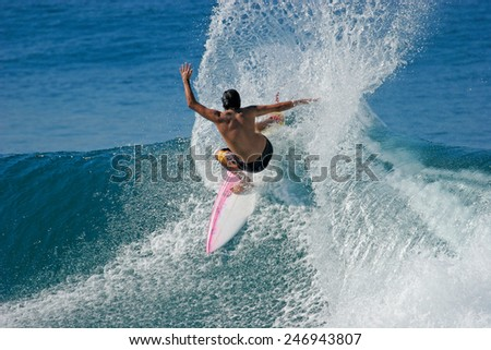 A surfer throws a huge plume of spray as he carves a radical off-the-lip. - stock photo